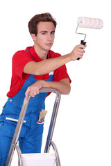 painter with roller brush standing on ladder