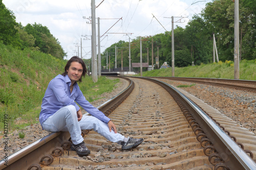 Man sitting on the railroad tracks