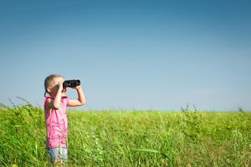 Little girl in the field looking away through binoculars