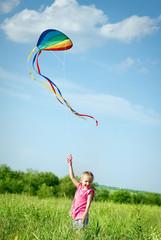 Little girl flying a kite in the field
