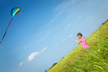 Back view of little girl flying a kite in the field