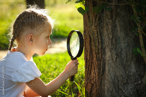 Little girl examining tree stem through the magnifying glass
