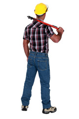Man holding wrench with back turned