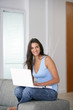 Young woman perched on a sofa with a laptop
