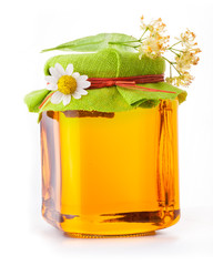 Honey in glass jar with flowers on white background