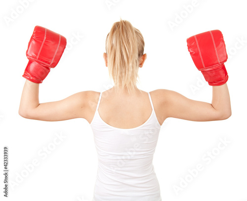 back of young woman wearing boxing gloves, white background
