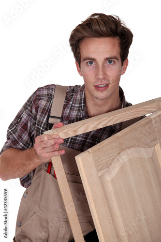 Young carpenter on white background