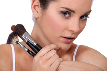 Woman with a selection of makeup brushes