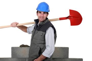 A mason holding a shovel.