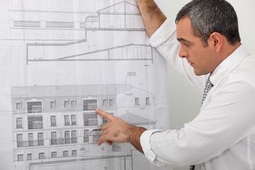 Architect examining a blueprint in detail