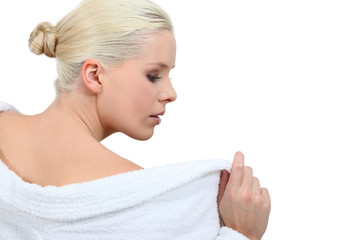 Woman taking off a white bathrobe