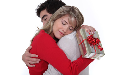 young man holding girlfriend in arms after giving present