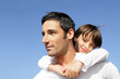 Boy riding piggy back on his father's back