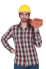 Builder holding stack of roof tiles