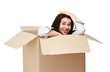 A smiling girl sitting in a cardboard box, isolated on white