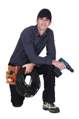 Handyman with power drill kneeling
