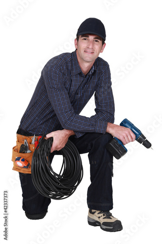 Handyman with power drill kneeling
