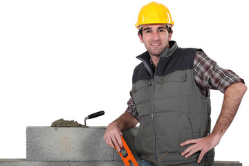 bricklayer posing near wall with arm akimbo