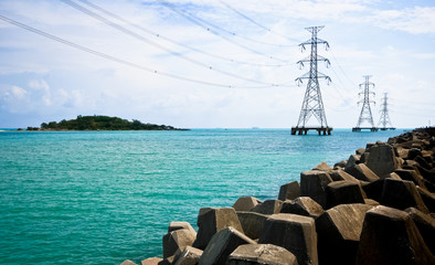 High voltage power pole in the sea and rock