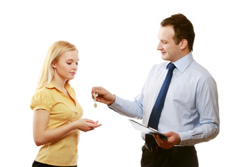 A male realtor giving keys to a woman