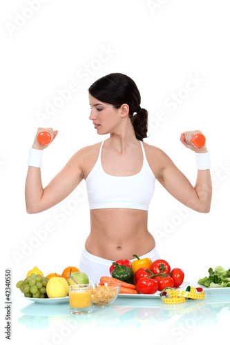 Woman lifting  weights surrounded by vegetables