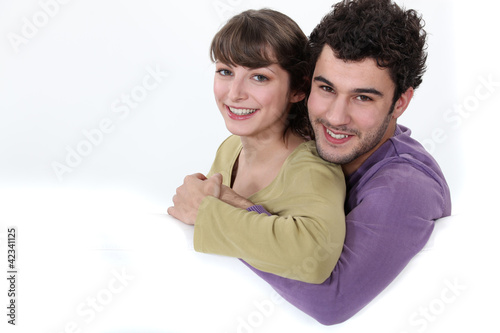Couple hugging on a white sofa