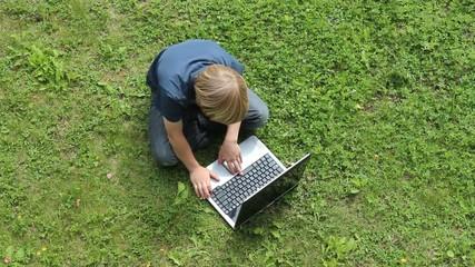 Kind mit Laptop in der Natur mit Vogelgezwitscher