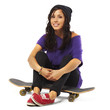 young happy woman sitting on a skateboard isolated