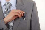 businessman putting a flash drive in his pocket