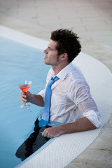 Young man having a drink in the pool