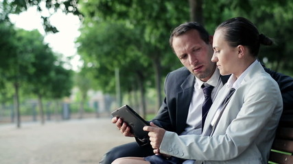 Business couple with tablet computer in the park, dolly shot