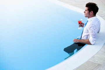 Young man having drink in the pool