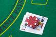 Ace of hearts and black jack with red poker chips