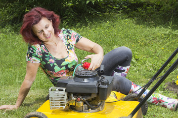 Smilling happy women oiling lawn mover