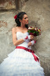 Beautiful bride with bouquet leaning against the wall (profile)