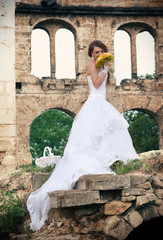 The bride standing in front of ruins with wedding bouquet