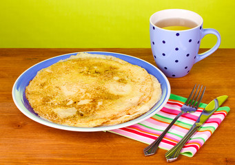 Stack of tasty pancakes on wooden table on green background