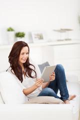frau sitzt mit tablet-pc auf dem sofa
