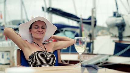 Happy glamour woman relaxing in marina, steadicam shot