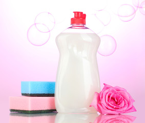 Dishwashing liquid with sponges and flower on pink background