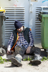 Tramp sleeping near dumpsters