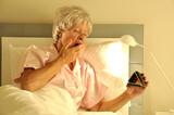 Fototapety Seniorin im Bett mit Wecker