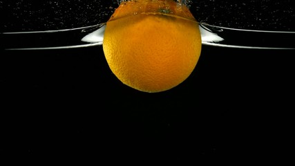 Orange in water on black background, Slow Motion
