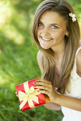 Beautiful teen girl with gift in the park at green grass.