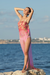 Girl in pink sarong with arms raised on the beach