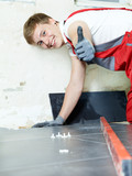 Handsome apprentice lays tiles and showing thumb up in site