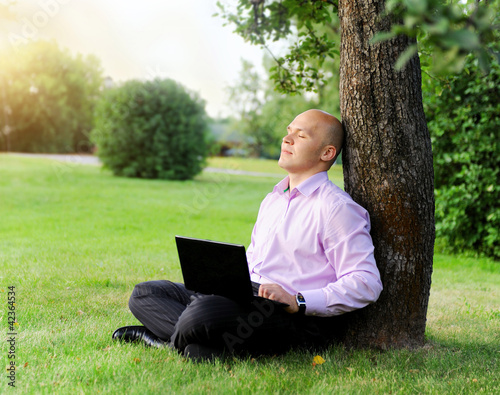 Businessman with laptop sitting near a tree