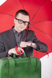 Young business man holding umbrella