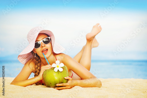 Young woman in pink swimsuit with coconut cocktail on the beach,