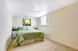 White large bedroom with green bed and art.